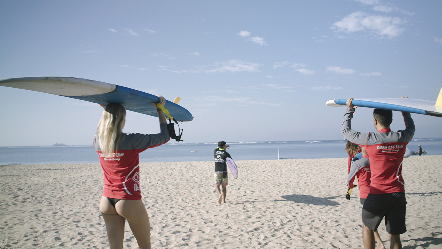 Surfers carrying their surf boards, led by an instructor