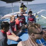 surf lesson with boat out to the reef